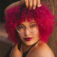 AJ Odneal poses with bright pink hair and glasses