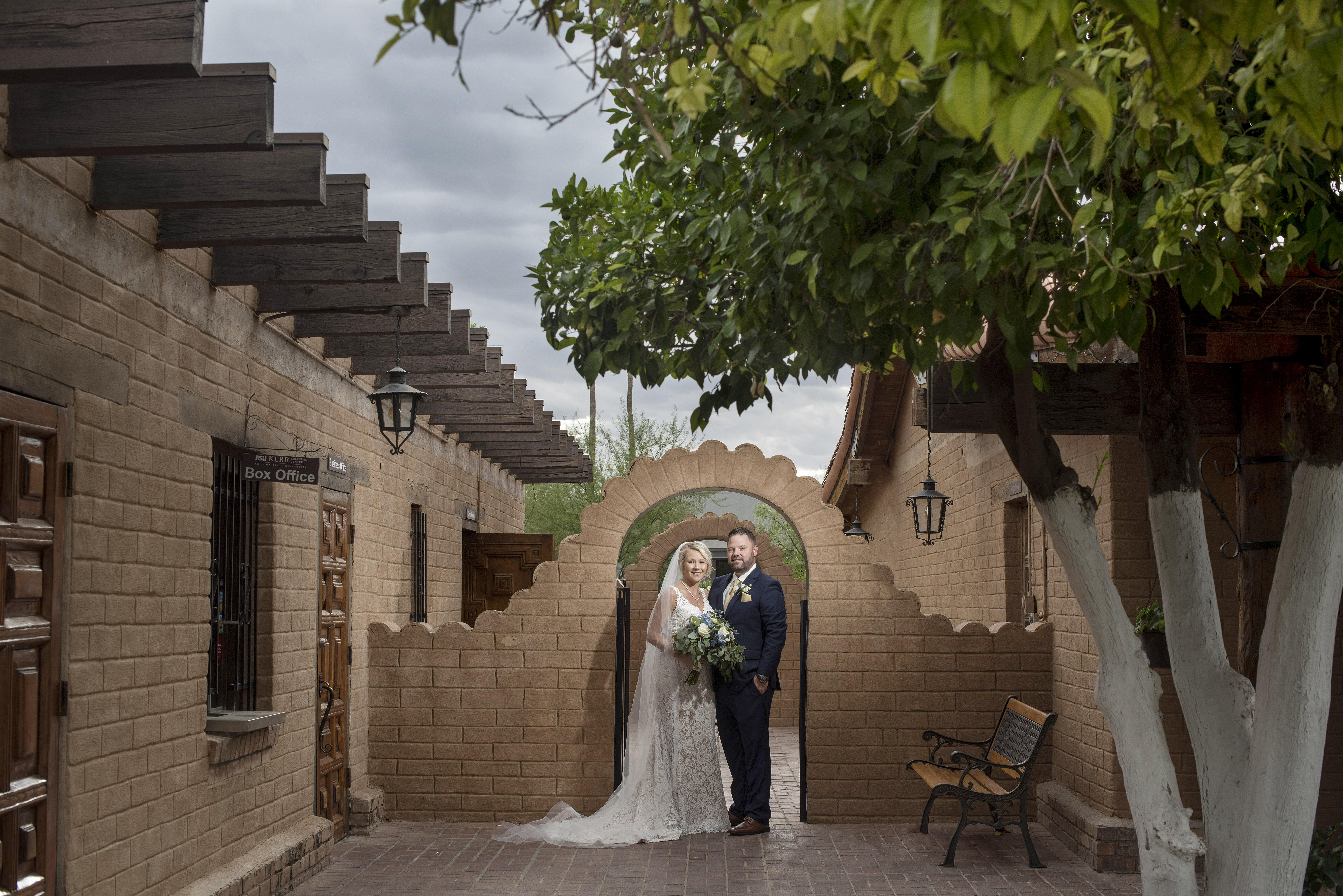 Married couple on wedding day in adobe archway