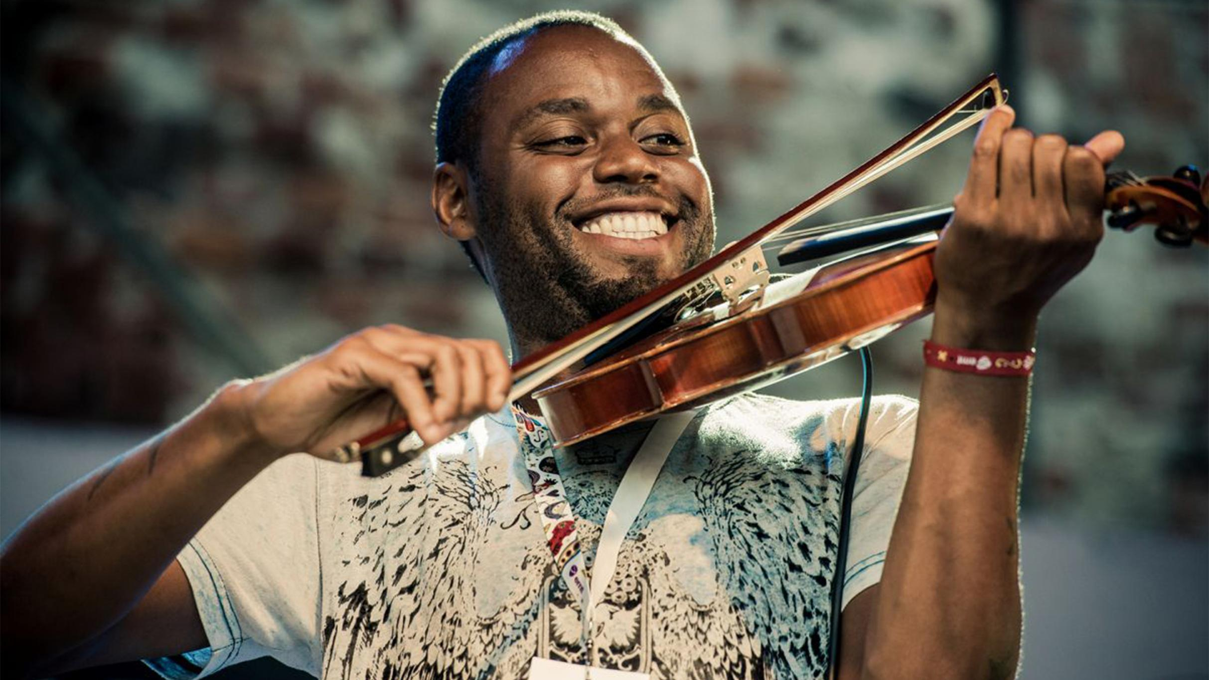 Cedric Watson smiles while performing.