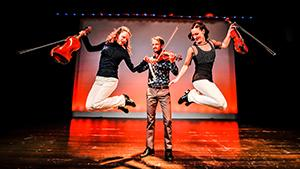 The Fitzgeralds play fiddle, dance and jump in the air onstage under bright stage lights