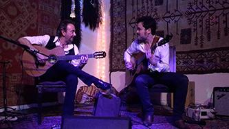 Guitars From Spain performing live - Jose Antonio Rodriguez and Twanguero play guitars together and smile at one another