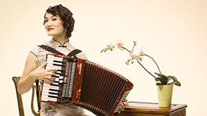 Jessica Fichot plays the accordion with a smile in a floral silk qipao