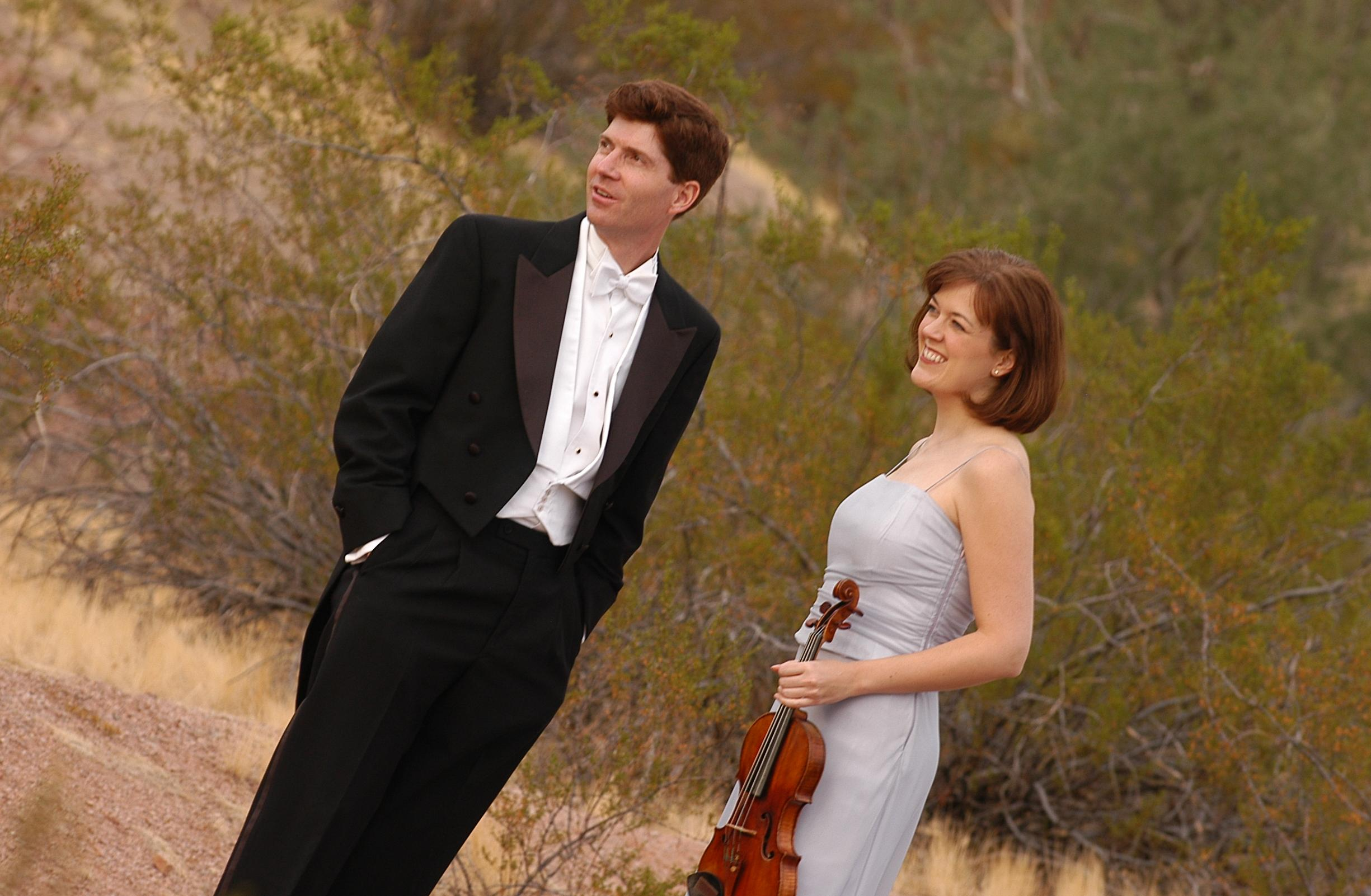 Katherine McLin and Andrew Campbell pose in the desert; Campbell is in a tuxedo and McLin holds a violin in a sparkly gown