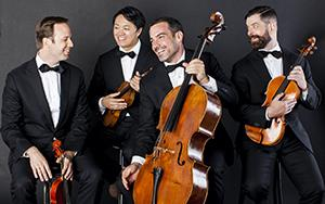 Miro Quartet poses in tuxedoes with their string instruments