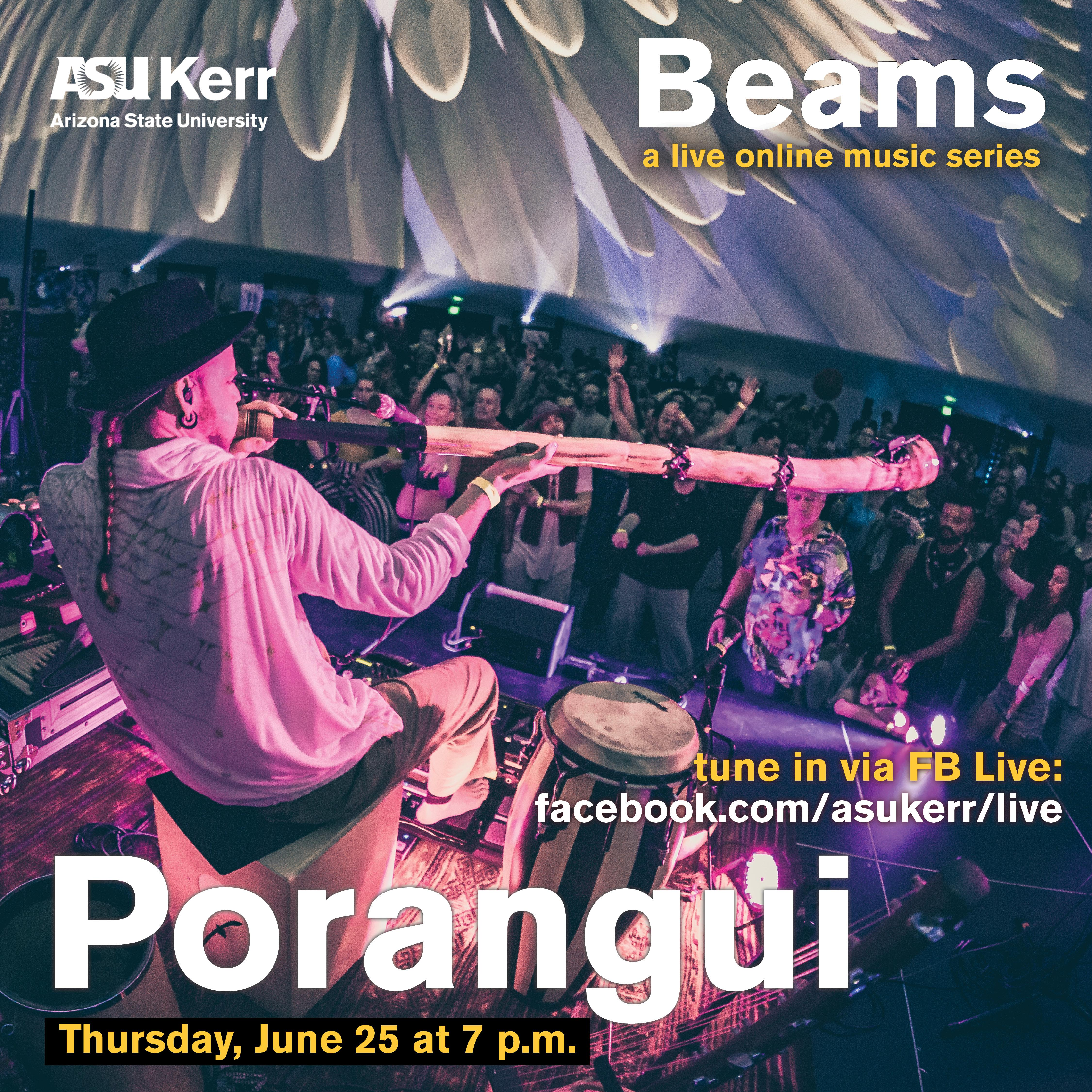 Porangui plays a digeridoo while seated among many different types of drums from around the world in front of a large indoor festival crowd