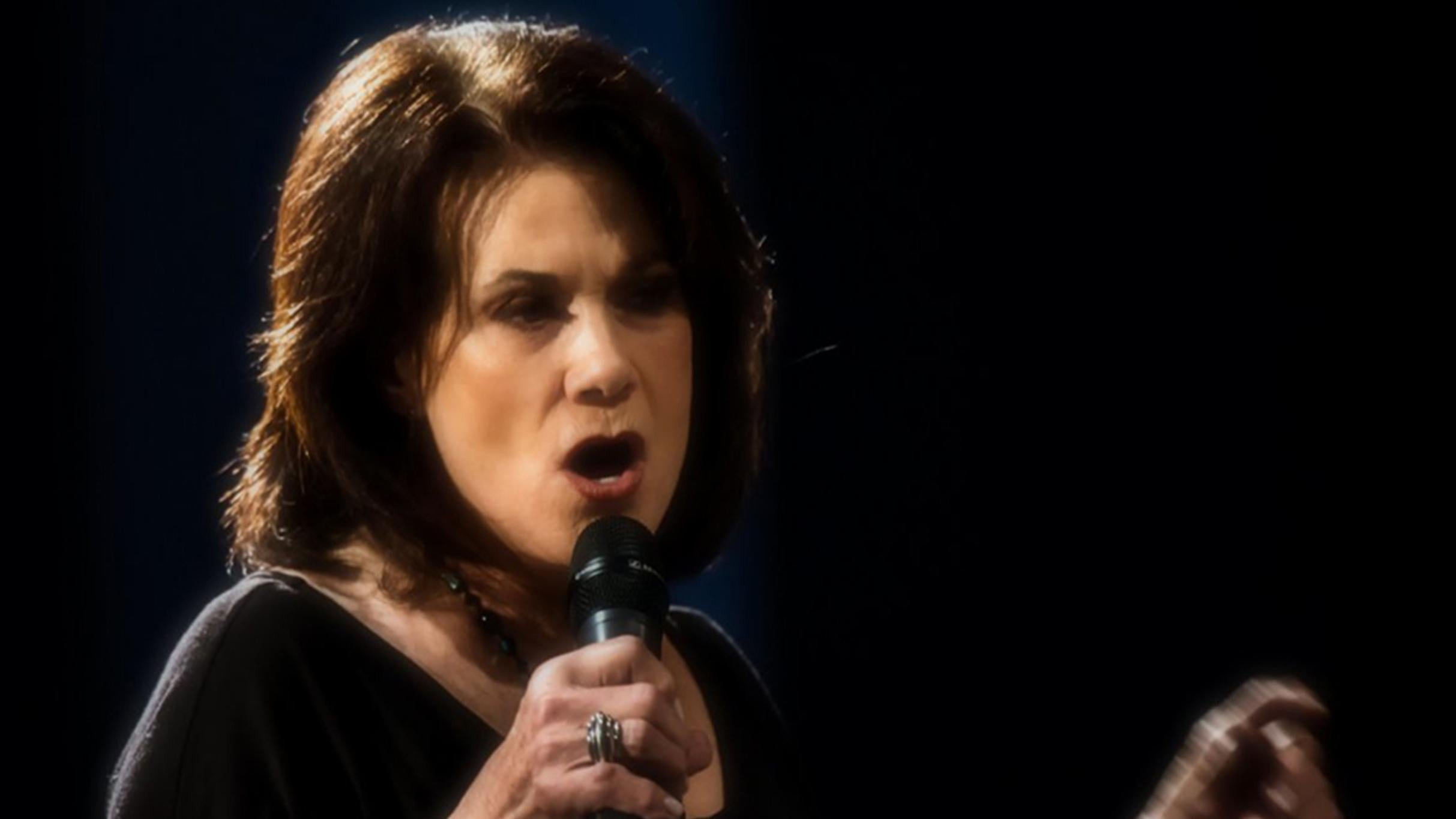 Ralna English singing on microphone.