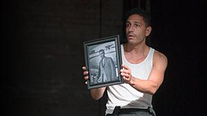 """Christopher Rivas performs in """"The Real James Bond...Was Dominican,"""" holding up a photo"""