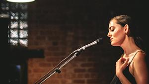 Grace Rolland, Rising Sun Daughter, performs live and sings into microphone