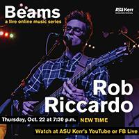 Rob Riccardo plays guitar and sings onstage under colorful lights