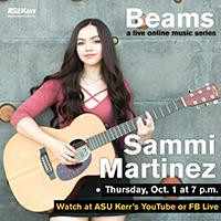 Sammi Martinez plays a chord on an acoustic guitar and smiles